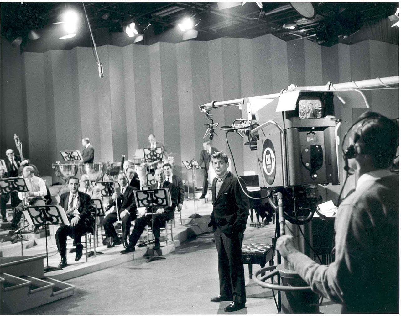 Leonard Bernstein with television camera. Leonard Bernstein with members of the Philharmonic rehearsing for a television broadcast 1958